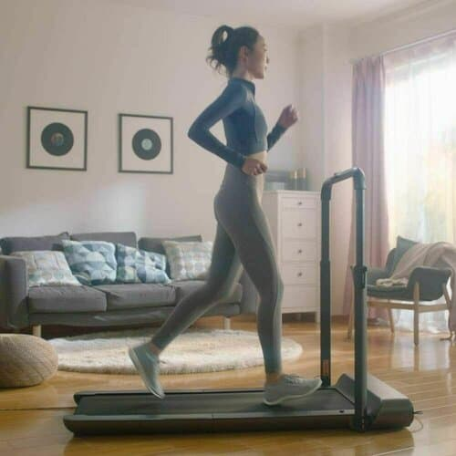 a lady running on walkingpad r1 pro in her house with furniture in the background