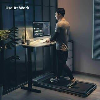 Man walking on treadmill while working on desktop
