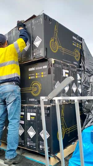 worker wearing reflective clothing is unloading a pallet full of factory refurbished segway ninebot max g30